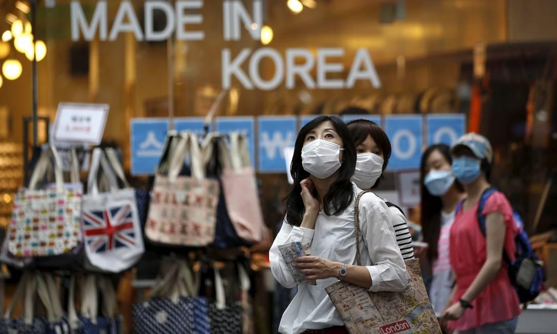 Turistas usam máscaras no distrito de compras de Myeongdong, centro de Seul. Esta semana a cidade recebeu alerta vermelho das autoridades, que desaconselharam viagens desnecessárias KIM HONG-JI / REUTERS