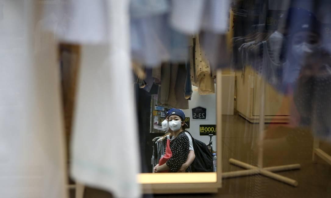 Casal passeia de máscara no centro de Seul. O surto de MERS forçou a Coreia do Sul a cortar as taxas de juros nesta quinta-feira, na esperança de suavizar o golpe na economia já sobrecarregada do pais. Autoridades relataram 14 casos novos da síndrome nesta quinta-feira KIM HONG-JI / REUTERS