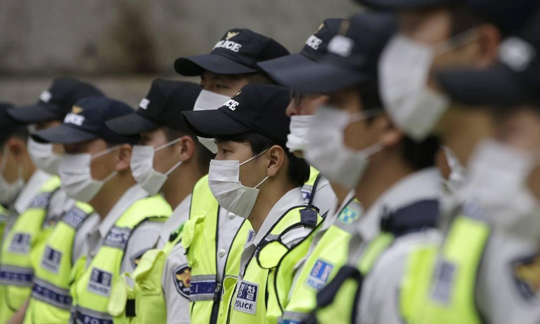 Policiais sul-coreanos usam máscaras para evitar MERS. Especialistas da OMS querem que as escolas sejam reabertas no país Lee Jin-man / AP