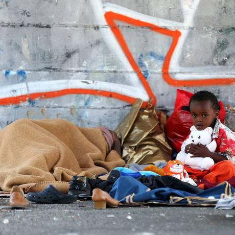 Criança se senta na rua enquanto sua mãe dorme ao lado da estação de Tiburtina, em Roma Foto: ALESSANDRO BIANCHI / REUTERS