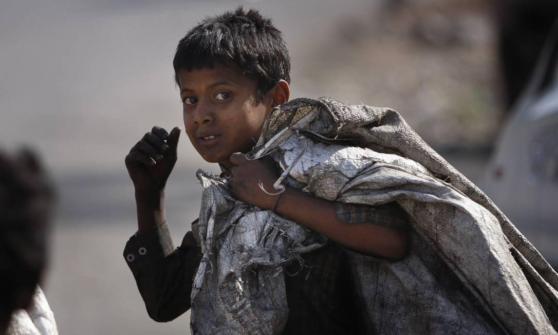 Menino trapeiro coleta material reciclável no Dia Mundial de combate ao Trabalho Infantil em Jammu, na Índia Channi Anand / AP