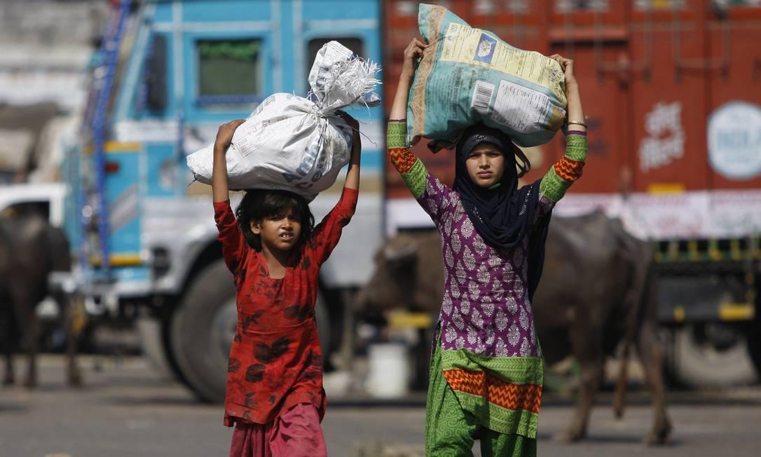 Crianças carregam sacos de vegetais e sobras coletadas em um mercado para vender em na favela em que vivem Channi Anand / AP