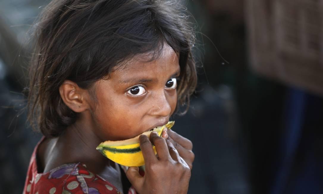 Criança come um pedaço de melão em um mercado de Jammu, na Índia Channi Anand / AP