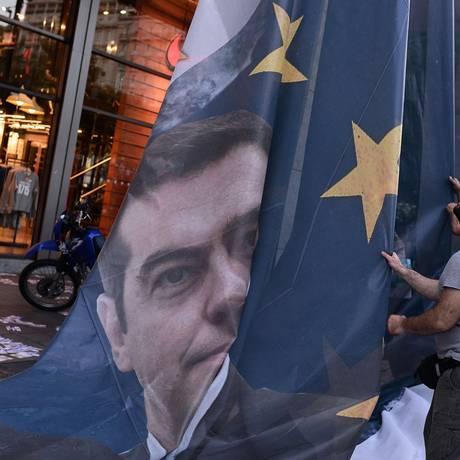 Manifestante em Atenas leva bandeira gigante com a foto do premier Alexis Tsipras Foto: Louisa Gouliamaki / AFP