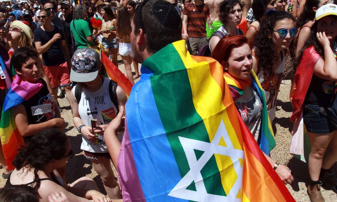 Bandeira do arco-íris com a estrela símbolo de Israel nos ombros de um simpatizante: maior evento do tipo em Tel Aviv GIL COHEN-MAGEN / AFP
