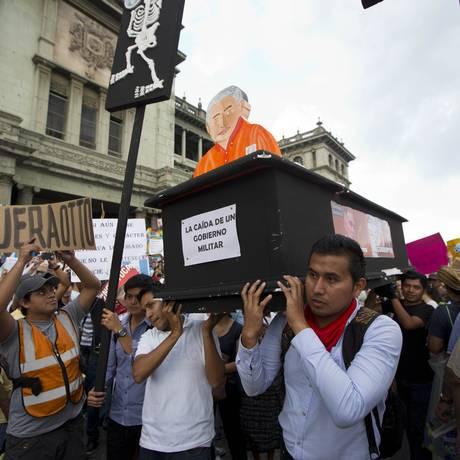 Manifestantes carregam um caixão que simboliza a renúncia do presidente: protestos contra corrupção acontecem todos os sábados na capital e em cidades do interior Foto: Moises Castillo / AP/30-05-2015