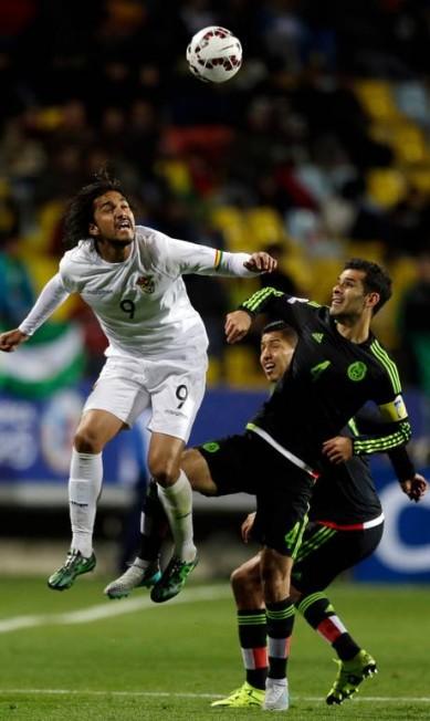 Ex-jogador do Flamengo e Cruzeiro, o boliviano Marcelo Moreno, à esquerda, disputa a bola com o zagueiro Rafael Marquez Ricardo Mazalan / AP