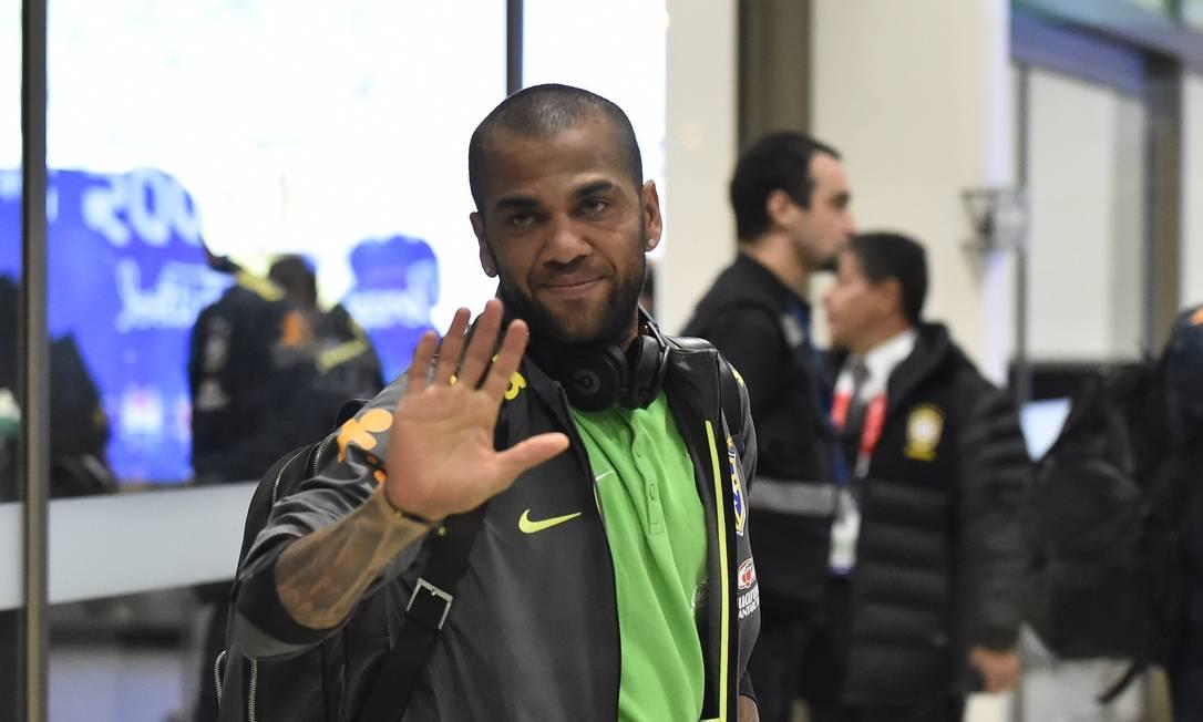 Convocado na quinta-feira, o lateral-direito Daniel Alves acena na chegada ao Chile RODRIGO BUENDIA / AFP