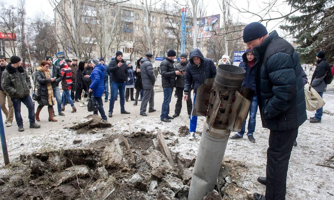 Conflito ucraniano preocupa EUA. Pessoas observam míssil que caiu em rua da cidade de Kramotorsk, na Ucrânia, em fevereiro deste ano Foto: VOLODYMYR SHUVAYEV / AFP