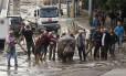 Homens tentam remover hipopótamo de rua alagada