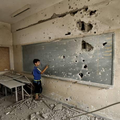 Menino palestino escreve em lousa crivada de balas em uma escola na Cidade de Gaza: ONU e organizações internacionais denunciam que Israel atingiu áreas civis durante conflitos no ano passado e mataram 500 crianças Foto: MOHAMMED ABED/AFP