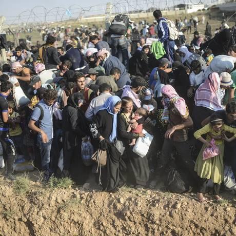 Famílias inteiras carregam o que podem e se arriscam na fronteira entre a Síria e a Turquia Foto: BULENT KILIC / AFP