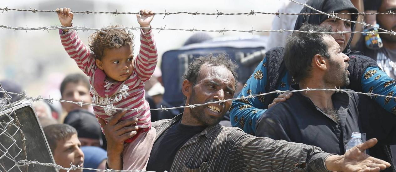 Um refugiado sírio reage enquanto espera atrás de cercas da fronteira turca Foto: UMIT BEKTAS / REUTERS