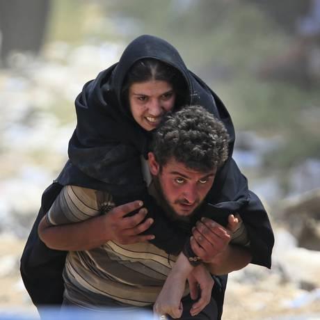 Um refugiado sírio carrega uma mulher doente em Akcakale, sudeste da Turquia, enquanto fogem intensos combates no Norte da Síria Foto: Lefteris Pitarakis / AP