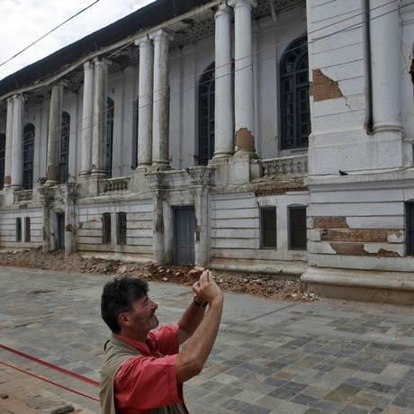 Turista fotografa construção danificada por terremotos que atingiram Katmandu, no Nepal Foto: Niranjan Shrestha / AP