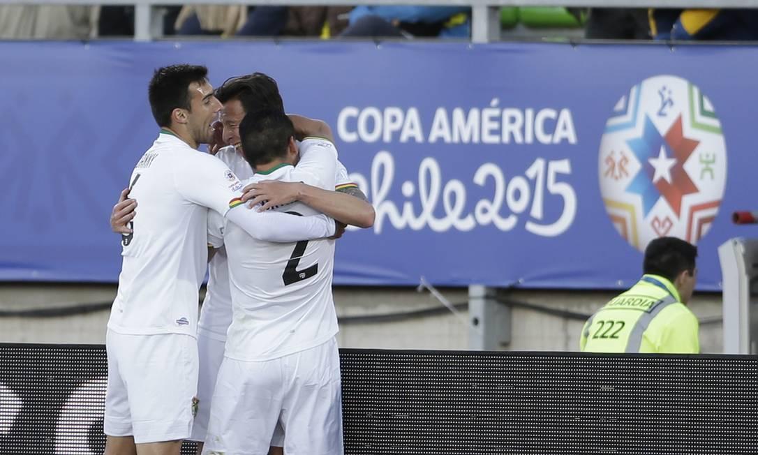 O boliviano Martin Smedberg, ao centro, é abraçado ao marcar na vitória sobre o Equador Jorge Saenz / AP