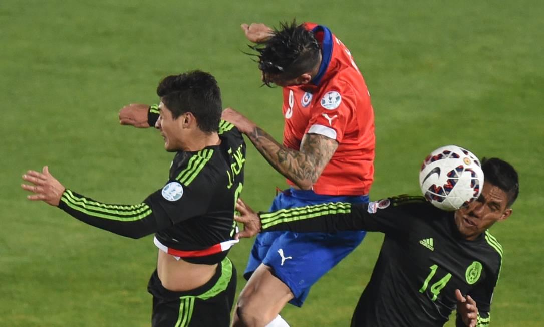 Em Santiago, O chileno Sanchez divide a bola entre os mexicanos Guemez e Valenzuela PABLO PORCIUNCULA / AFP