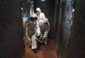 Funcionários desinfectam karaokê em Seul, na Coreia do Sul Foto: Lee Jin-man / AP