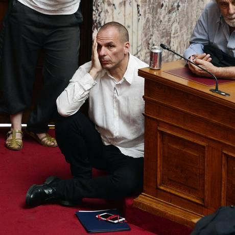O ministro das Finanças grego, Yanis Varoufakis, ouve o primeiro-ministro Alexis Tsipras discursar no Parlamento Foto: LOUISA GOULIAMAKI / AFP