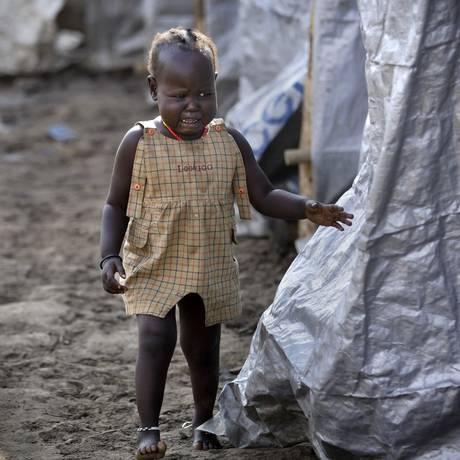 Menina sul-sudanesa procura parentes em campo de refugiados em Juba, em 2013 Foto: Ben Curtis / AP
