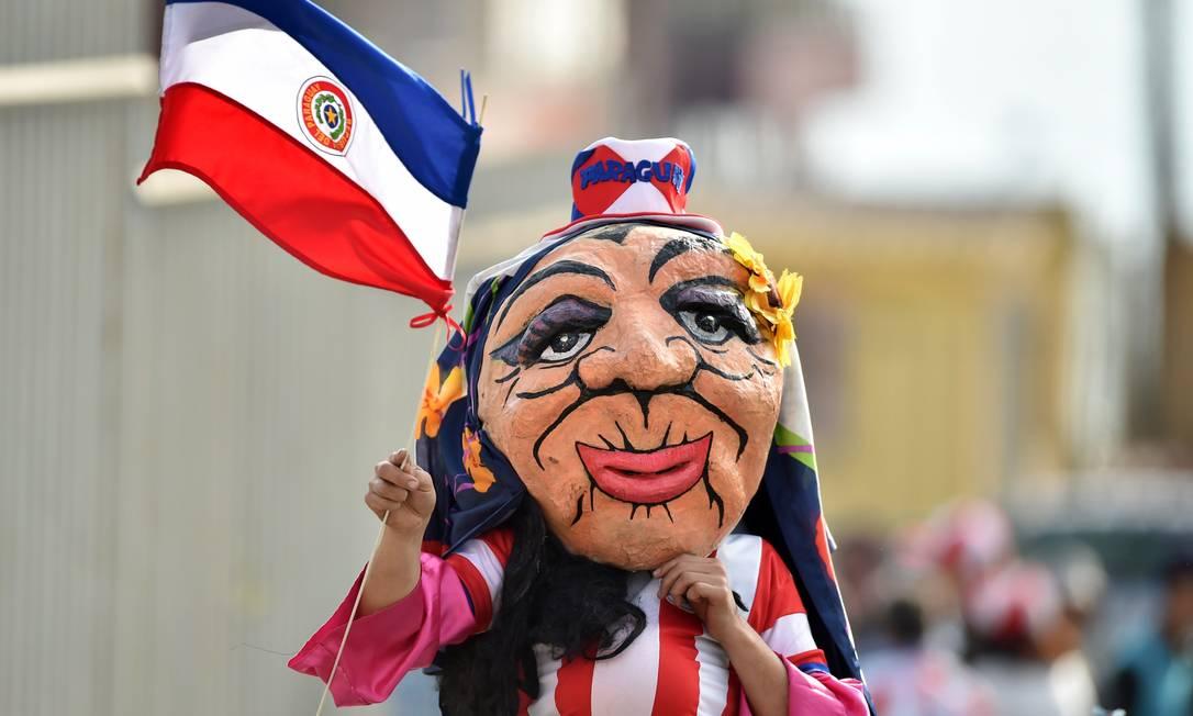 Baile de máscaras? Torcedora do Paraguai também escondeu o rosto na chegada ao estádio YURI CORTEZ / AFP