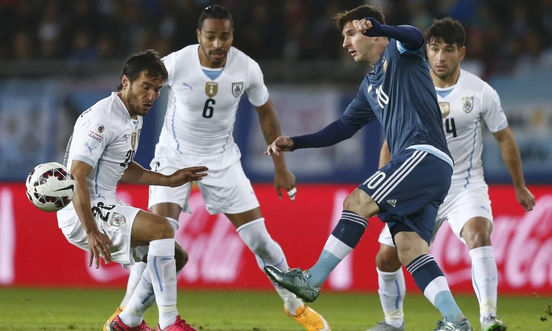 O argentino Messi chuta a bola, marcado por Alvaro Gonzalez em La Serena MARCOS BRINDICCI / REUTERS