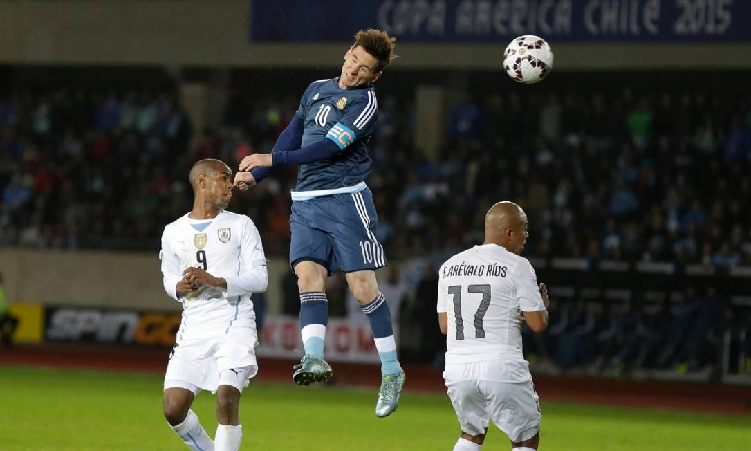 O argentino Messi cabecei a a bola, marcado pelos uruguaios Rolan, e Arévalo-Rios Natacha Pisarenko / AP