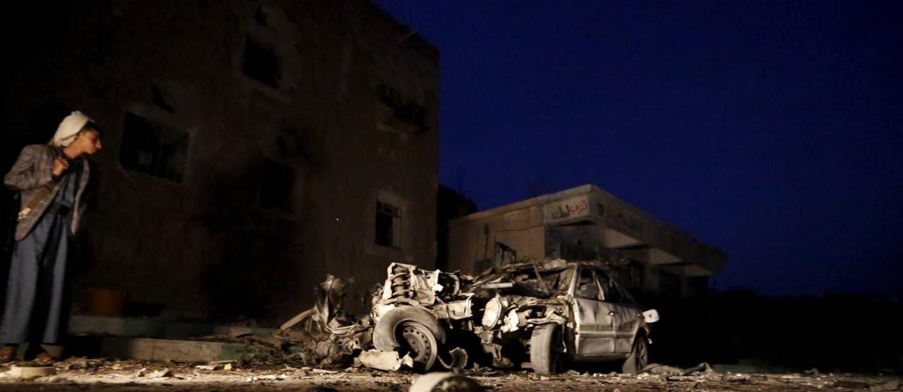 Um homem observa o que restou de um dos carros-bomba, em Sanaa Foto: KHALED ABDULLAH / REUTERS