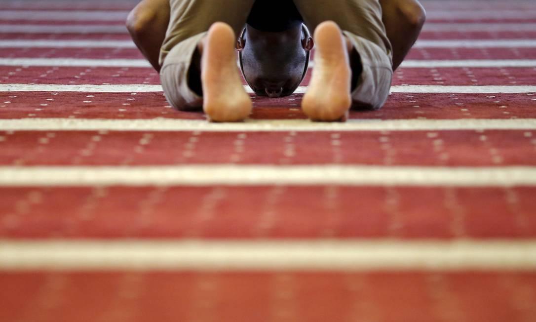 Com a cabeça encostada no chão, um homem ora antes de o Ramadã começar, na mesquita Assafaah, em Singapura EDGAR SU / REUTERS