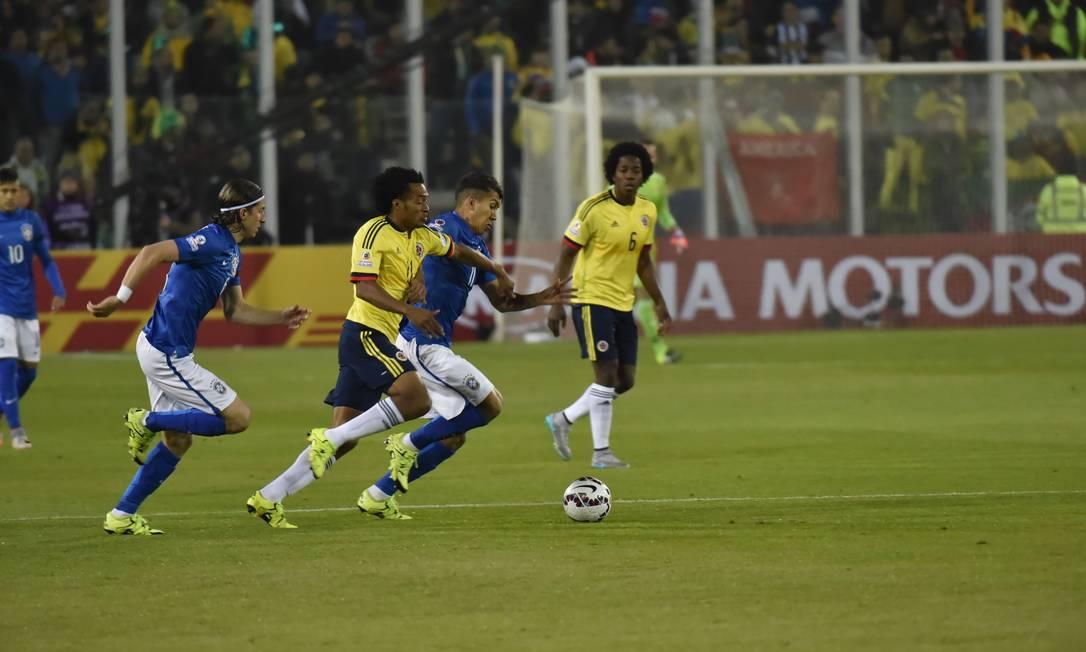Colombiano Cuadrado disputa a bola com Filipe Luis e Firmino NELSON ALMEIDA / AFP
