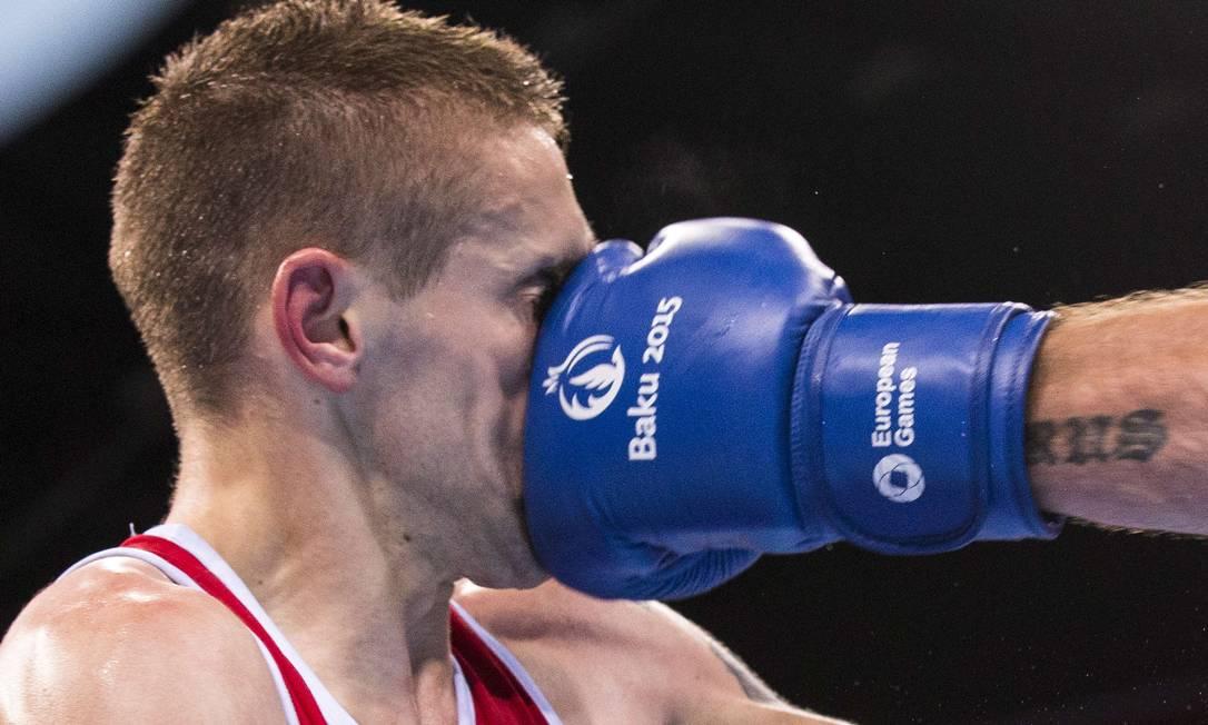 Matteo Komadina, da Croácia, recebe um golpe durante a luta contra o israelense Igor Lazarev, no boxe categoria 60 Kg JACK GUEZ / AFP