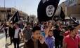 Manifestantes criam slogans favoráveis ao Estado Islâmico, enquanto carregam bandeiras do grupo, em frente à sede do governo provincial em Mosul, no Iraque