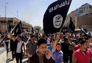 Manifestantes criam slogans favoráveis ao Estado Islâmico, enquanto carregam bandeiras do grupo, em frente à sede do governo provincial em Mosul, no Iraque Foto: AP