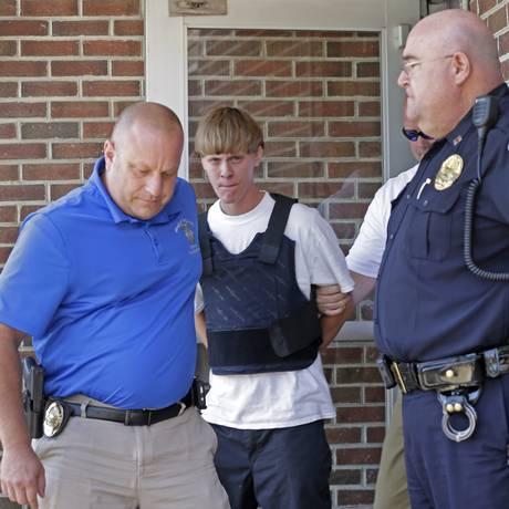 Dylann Roof é escoltado por policiais até audiência após ser flagrado Foto: Chuck Burton / AP