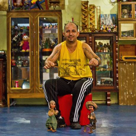 Mestre Grilo com dois fantoches do acervo de brinquedos do Centro Cultural Lottus, que ele administra junto com a mulher. Os fantoches são do século XIX para XX Foto: Bia Guedes / Agência O Globo
