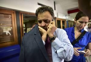 Senador Aécio Neves conversa no celular na área de saída do aeroporto internacional de Caracas Foto: CARLOS BECERRA / AFP