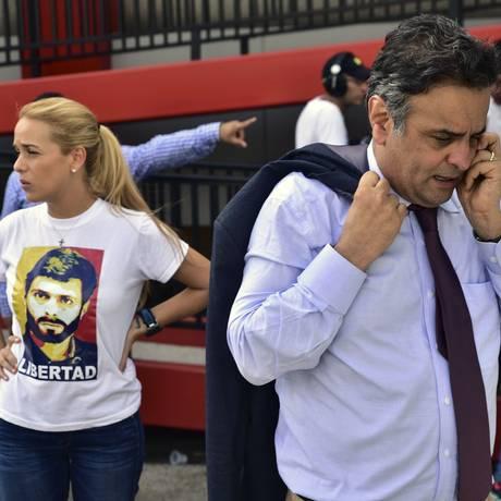 No aeroporto de Caracas, senador Aécio Neves conversa no telefone próximo a mulher do líder opositor preso Leopoldo López Foto: CARLOS BECERRA / Agência O Globo