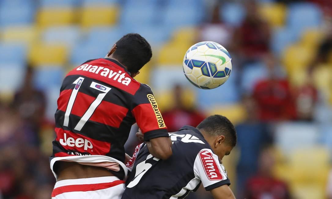 Gabriel, do Fla, divide a bola com um jogador do Galo Guito Moreto / Agência O Globo