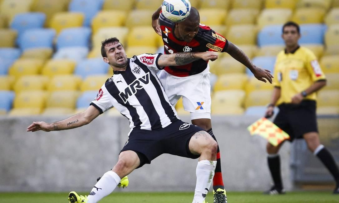 Samir cabeceia a bola, marcado por Lucas Pratto Guito Moreto / Agência O Globo