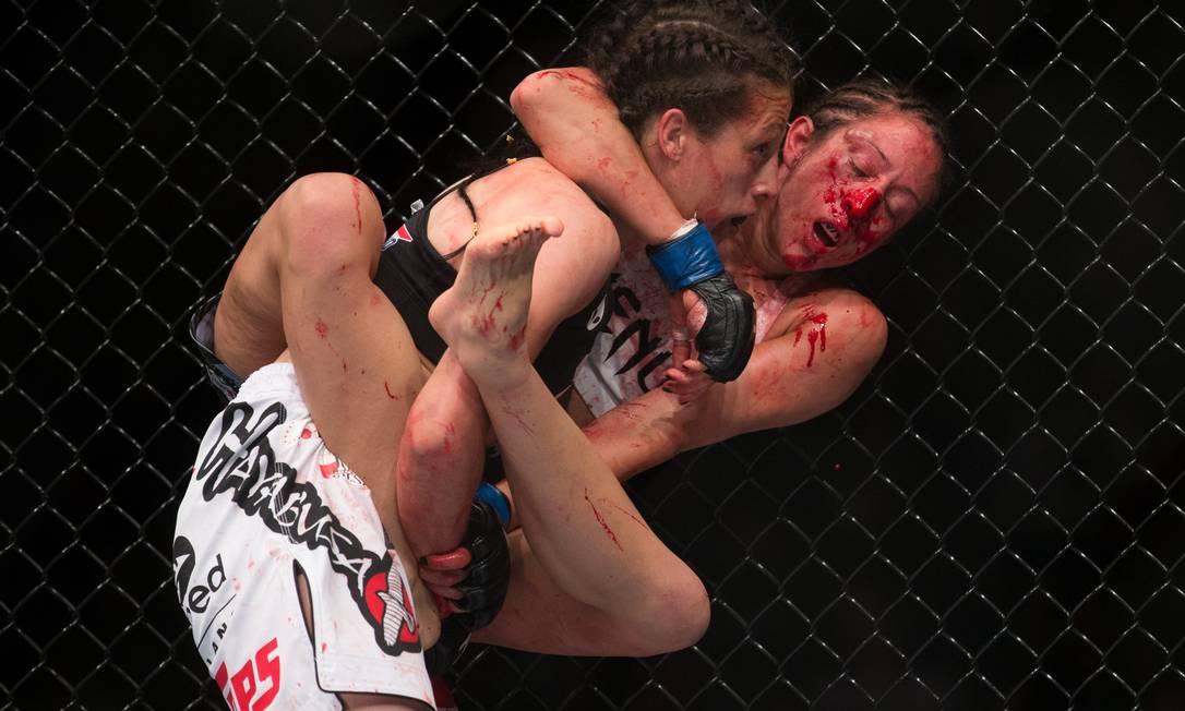 Junto à grade do octógono, Jessica Penne se agarra à campeã Joanna Jedrzejczyk, tentando a finalização. Americana, porém, acabou nocauteada pela polonesa no UFC em Berlim Axel Schmidt / AP
