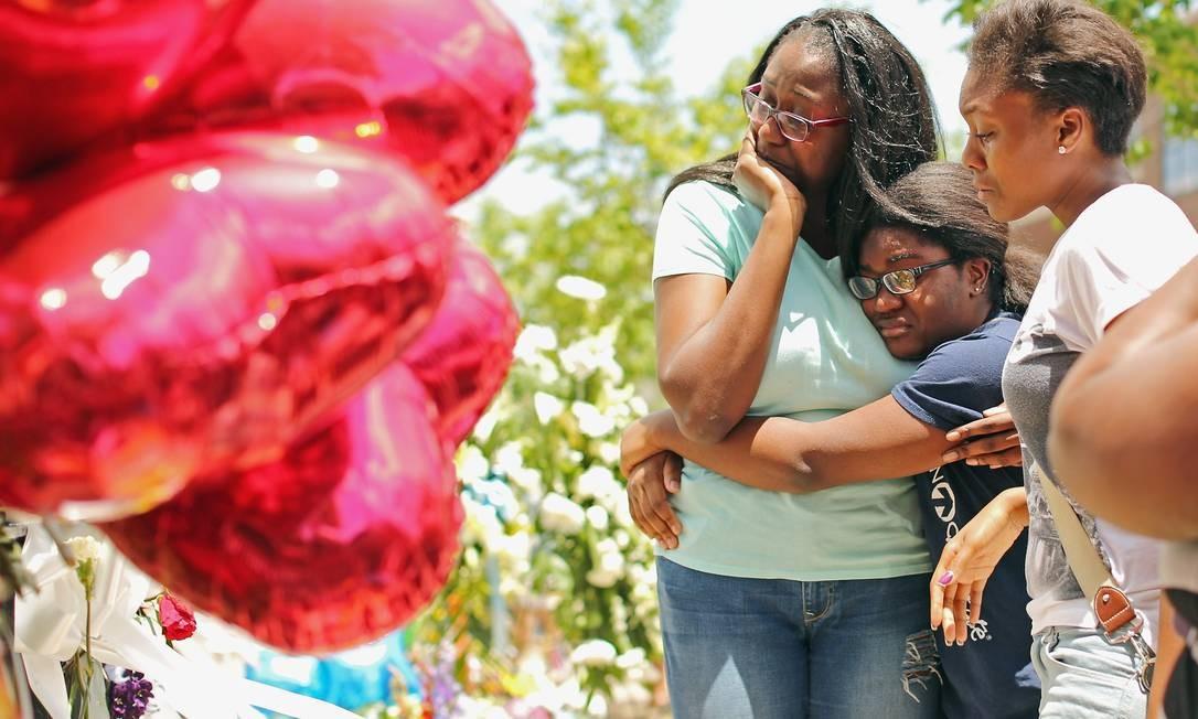 Luto. Parentes de uma das vítimas visitam o memorial diante da igreja em Charleston, na Carolina do Sul Foto: CHIP SOMODEVILLA / AFP
