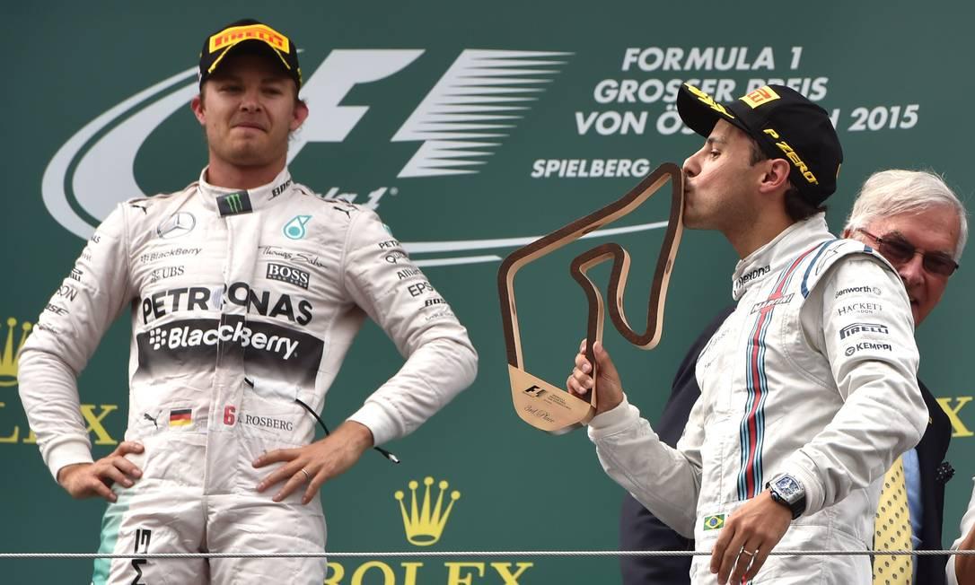 Observado por Rosberg, Massa beija o troféu ANDREJ ISAKOVIC / AFP