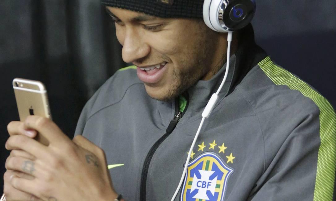 Neymar, ligado no celular e no fone de ouvido, acompanha a seleção no Estádio Monumental de Santiago, contra a Venezuela. Ele está suspenso JORGE ADORNO / REUTERS