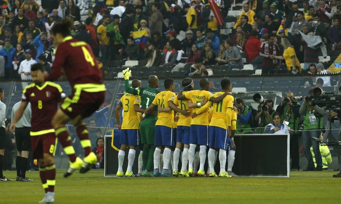 A seleção brasileira posa para fotos enquento jogadores venezuelanos se aquecem Luis Hidalgo / AP