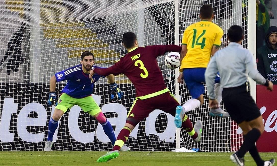Thiago Silva no momento em que se antecipa ao zagueiro da Venezuela e bate de chapa para marcar, com categoria MARTIN BERNETTI / AFP