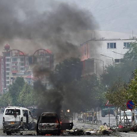 A fumaça sobe de veículos queimados no local do ataque em frente ao prédio do parlamento afegão Foto: Shah Marai / AFP