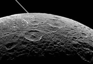 Detalhe da superfície da lua Dione, com os aneis de Saturno ao fundo Foto: NASA/JPL-Caltech/SSI