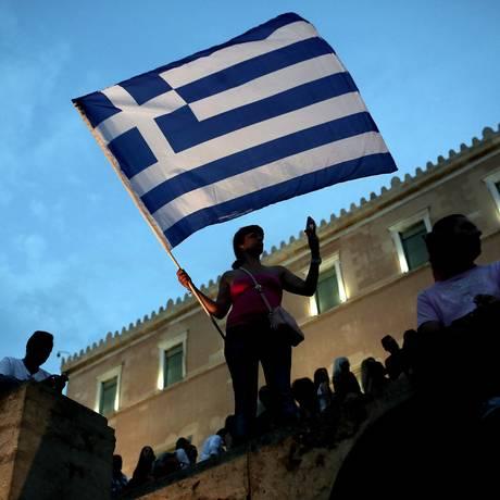 Manifestante contrária ás às medidas de austeridade na Grécia protesta em frente ao Parlamento neste domingo Foto: Angelos Tzortzinis / AFP