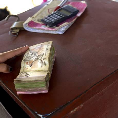 Um maço de notas de 100 bolívares é colocado sobre a mesa de um operador do mercado negro de dólares, em Cucuta, na Venezuela Foto: Alejandra Parra / Bloomberg