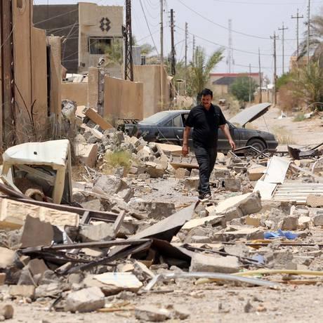 Um homem iraquiano caminha em meio a escombros depois de voltar para sua casa destruída em combates contra o Estado Islâmico em Tikrit, a 130 quilômetros ao norte de Bagdá, no Iraque Foto: Hadi Mizban / AP